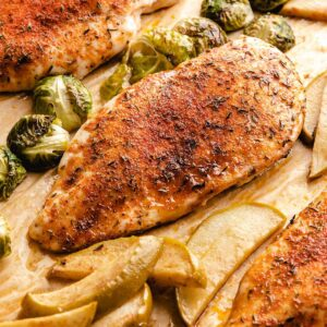 Roasted chicken breasts, apple slices and Brussels sprouts on a sheet pan.