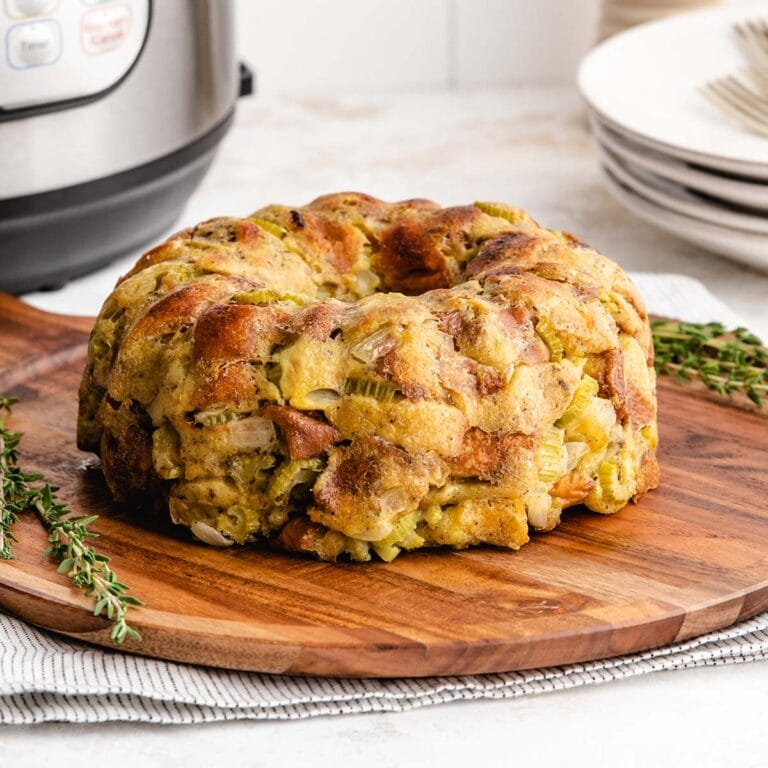Bundt pan stuffing on a decorative round wooden board, placed in front of an Instant Pot.