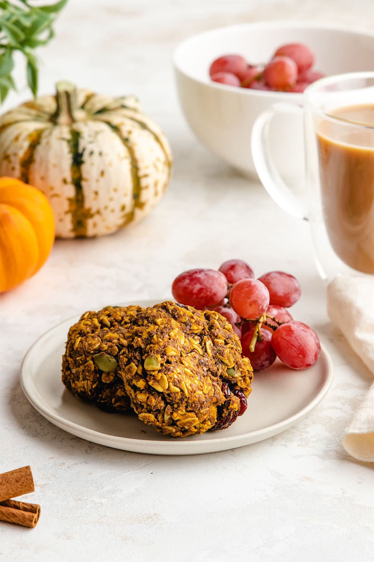 Two Pumpkin Breakfast Cookies and a small bunch of red grapes on a small cream-coloured plate.