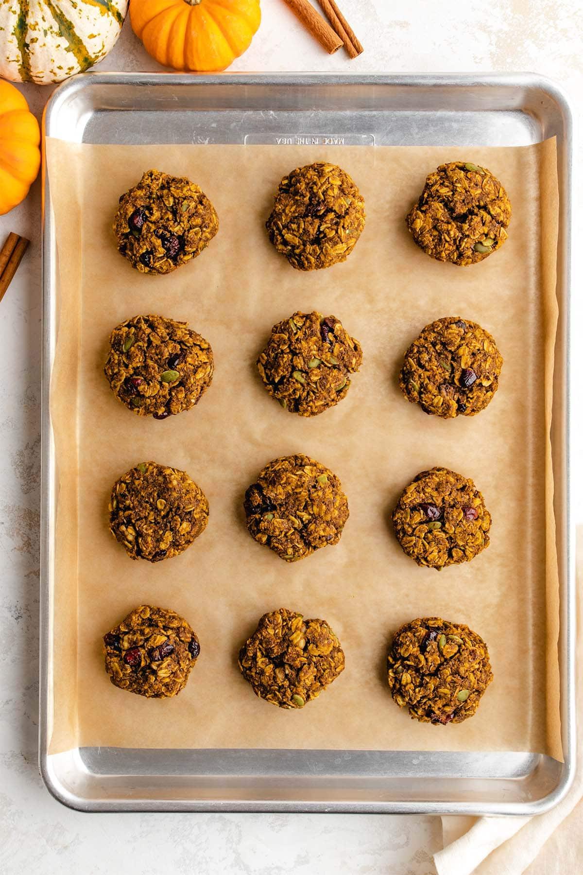Twelve Pumpkin Breakfast Cookies on a parchment-lined baking sheet.